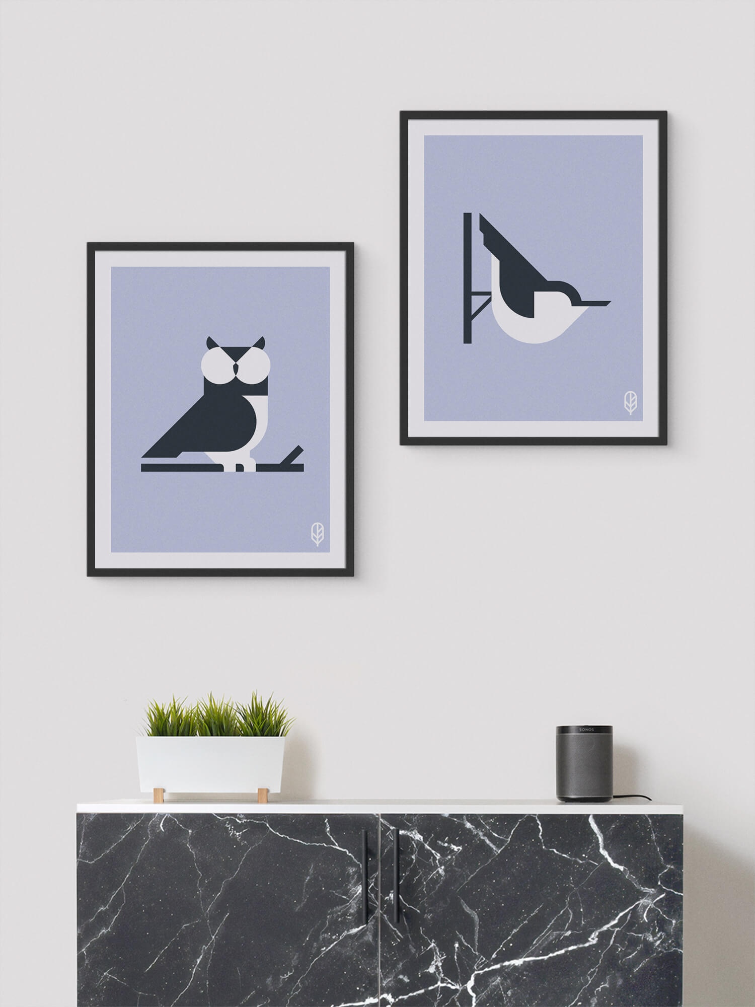 Two framed Flock Together prints displaying the illustrations of an owl and a nuthatch on the wall of a modern apartment