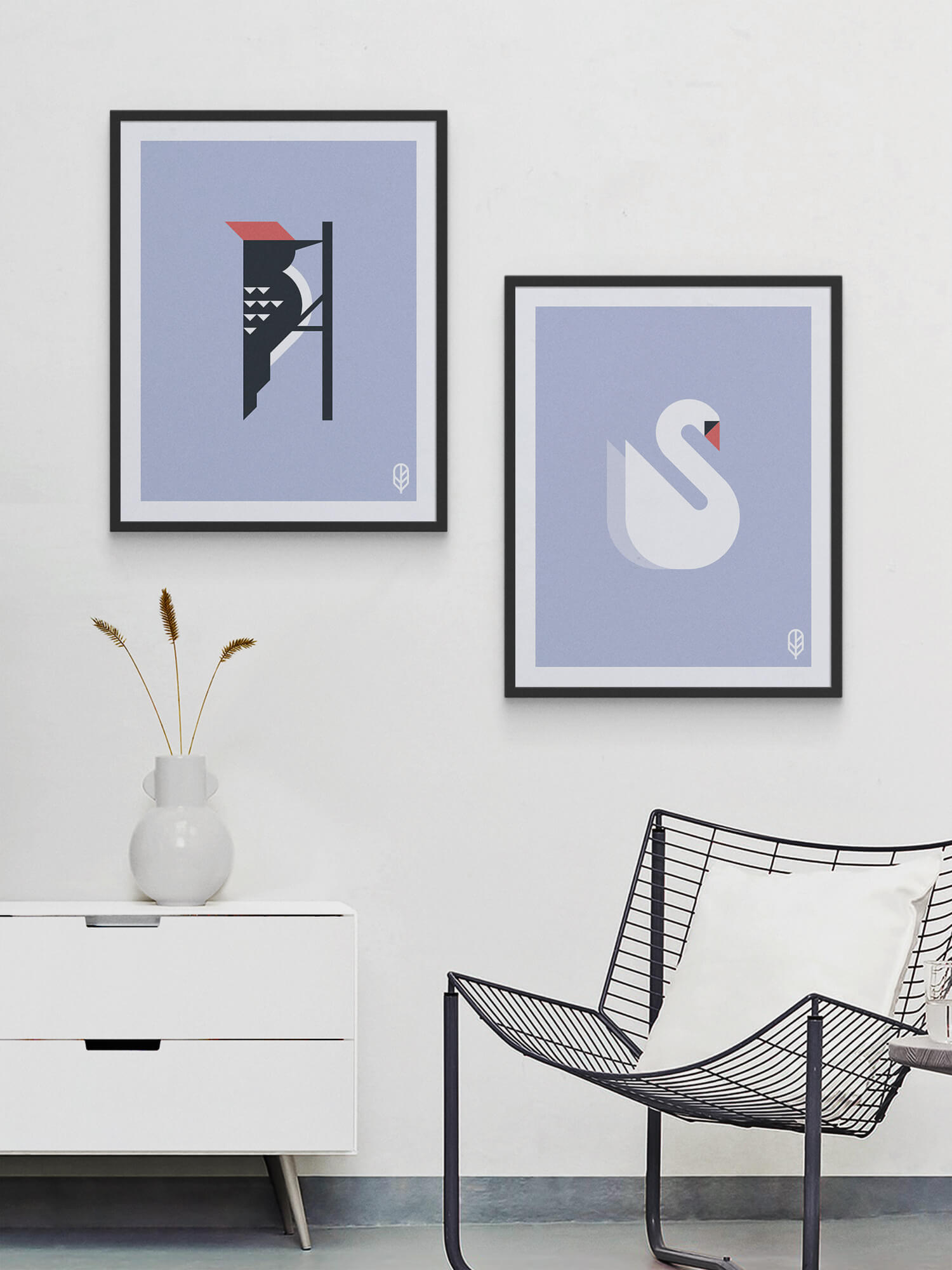 Two framed Flock Together prints displaying the illustrations of a woodpecker and a swan on the wall of a modern apartment