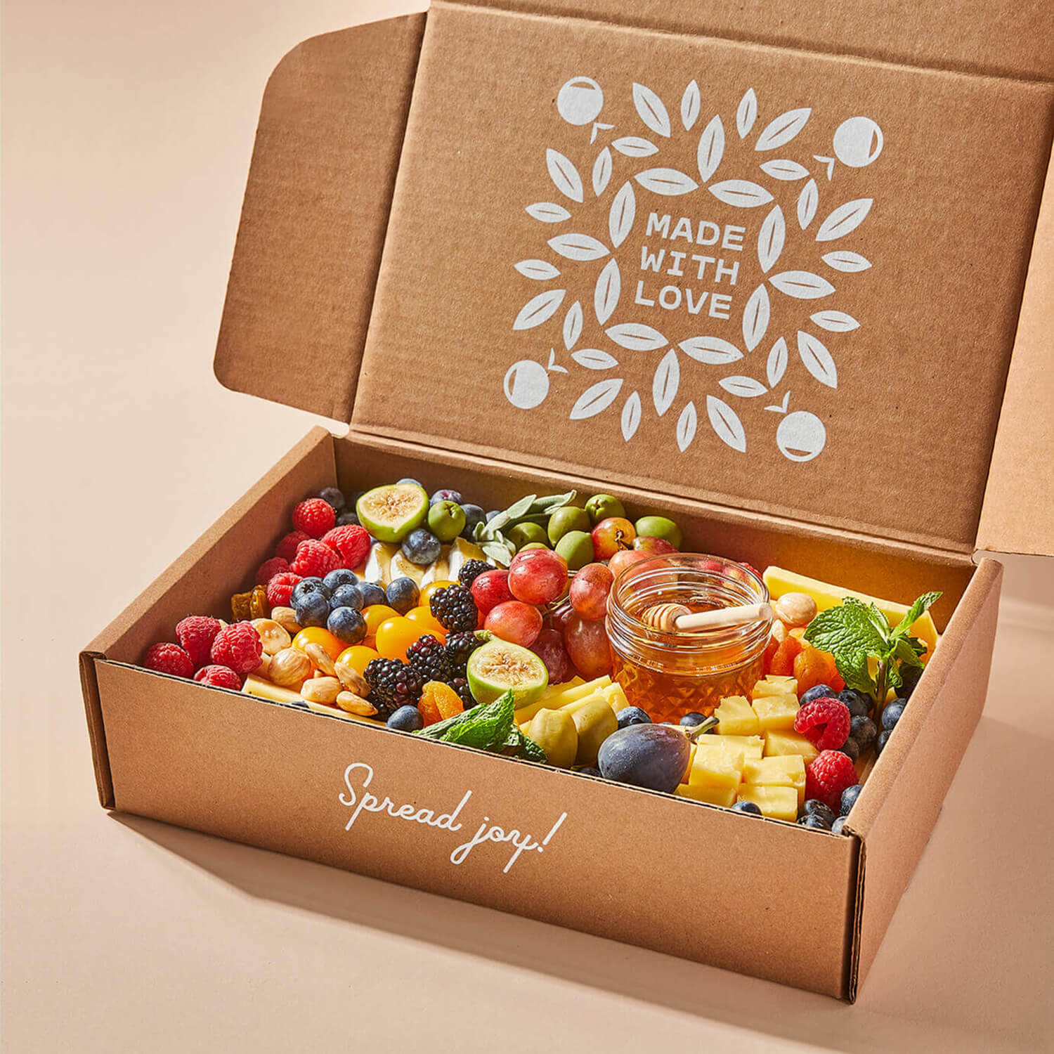 Angled view of an open medium Grazy box containing cheeses and fruits