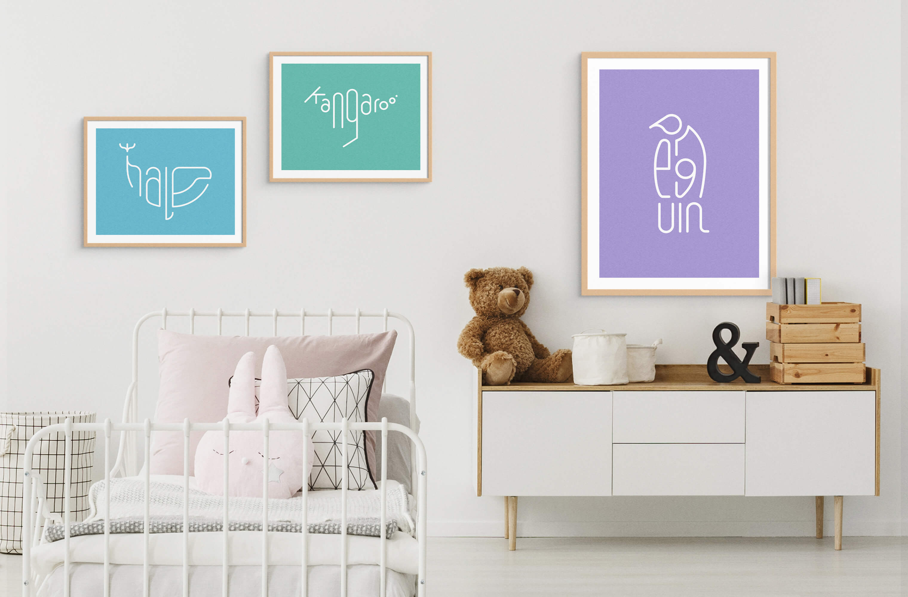 Three framed Word Animals prints displaying the illustrations of a whale, kangaroo and penguin on the wall of a childs room